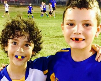Two young boys on a sports field wearing their custom mouthguards for Bisbane's Denture Health Care Clinic