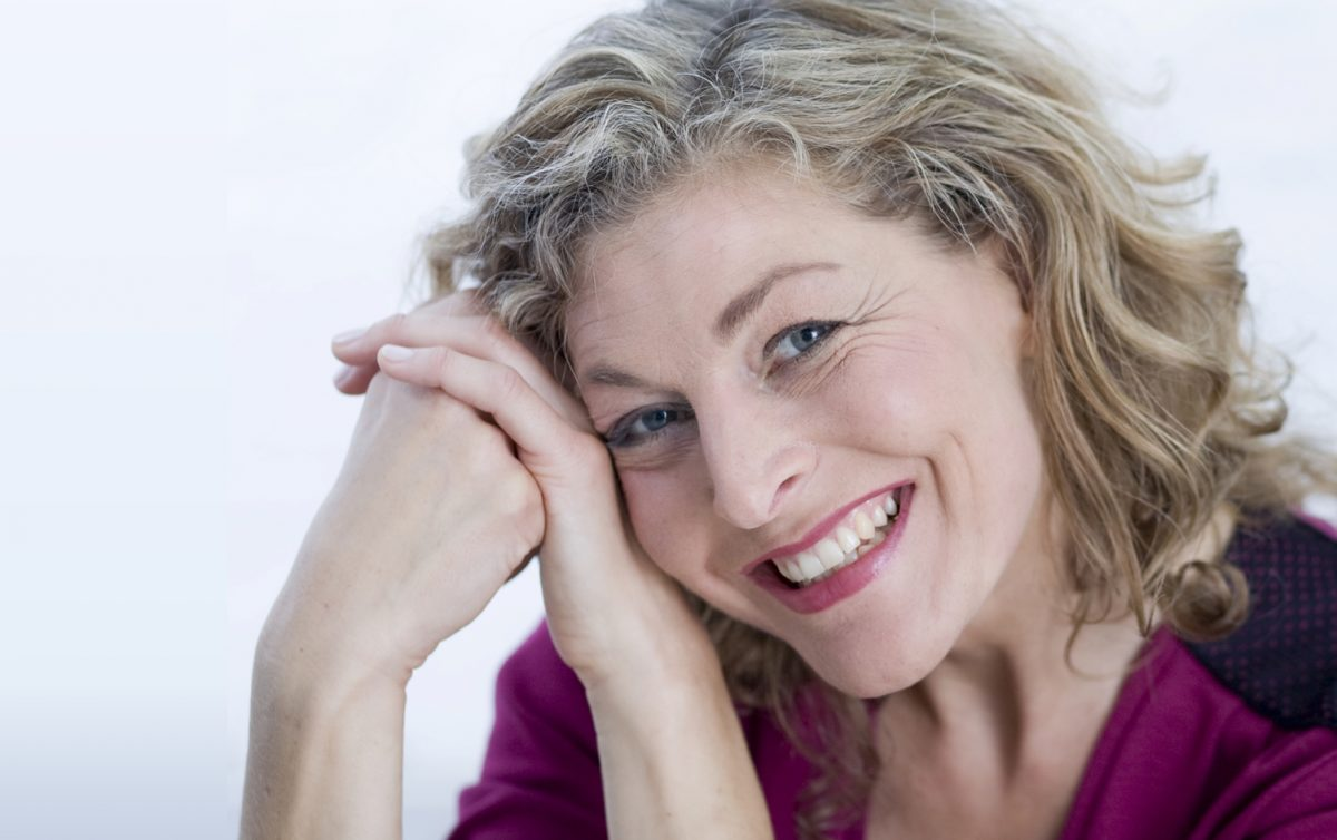 What to expect when getting dentures blog featured image - smiling middle aged woman