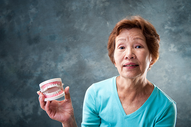 A senior lady holding a set of dentures