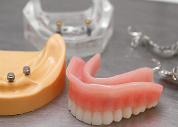 Dentures on table top | Featured image for Things to Know About Dentures blog.